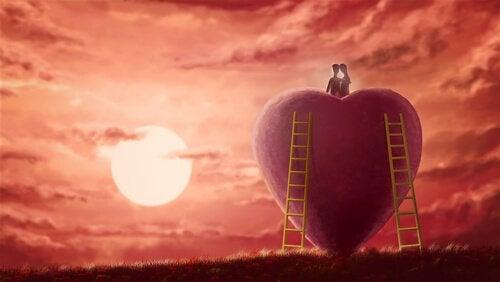 Coppia seduta sopra un cuore che guarda il tramonto