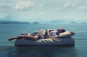Le fasi del sonno e donna su un materasso in mezzo al mare