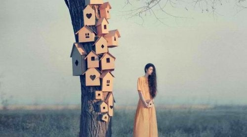 Donna vicino ad un albero con delle casette, mentre pensa a come farsi rispettare