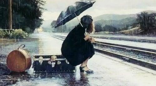 Donna alla stazione sotto la pioggia