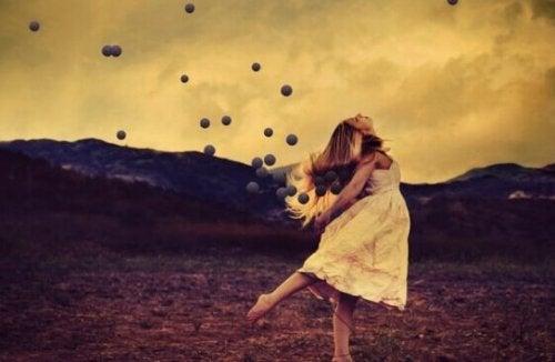 Ragazza che balla circondata da sfere, come rappresentazione dell'affrontare il vivere senza una famiglia