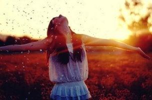 Una donna che apre le braccia paradosso della felicità
