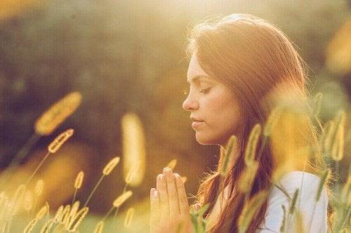 Donna con gli occhi chiusi mentre medita per fare spazio al nuovo