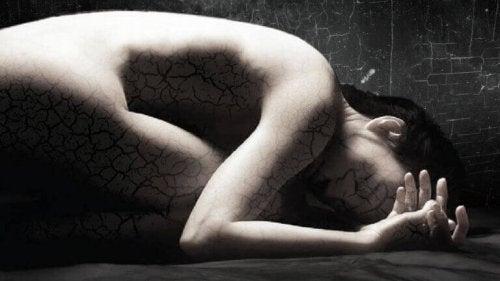 Donna rannicchiata e con crepature nel corpo