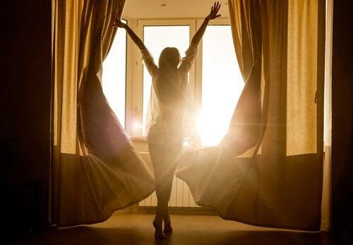Donna che si sveglia e apre le finestre