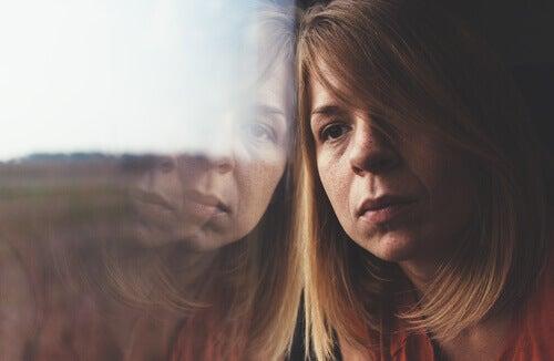 Donna triste appoggiata ad una finestra che pensa ai suoi sogni