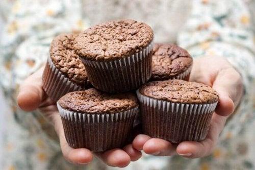 Mani che tengono cinque muffin