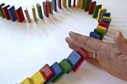Mano che blocca l'effetto domino