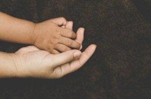 Mano di bambino adottato che tiene quella della madre