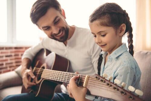 Bambina e papà che suonano la chitarra