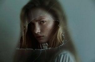 Ragazza arrabbiata dietro ad un vetro rotto