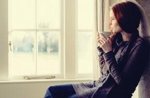 Ragazza che guarda fuori dalla finestra e le pause