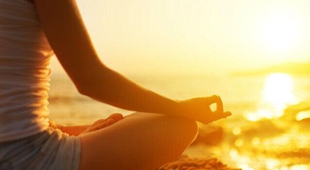 Ragazza che usa mantra per meditare davanti al mare