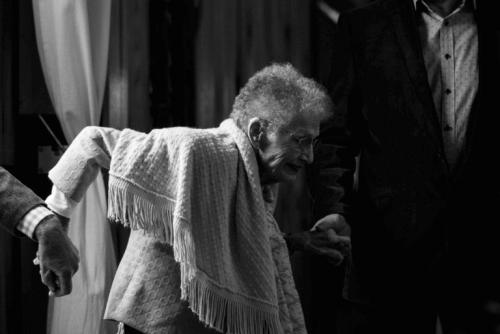 Uomini che aiutano una donna anziana