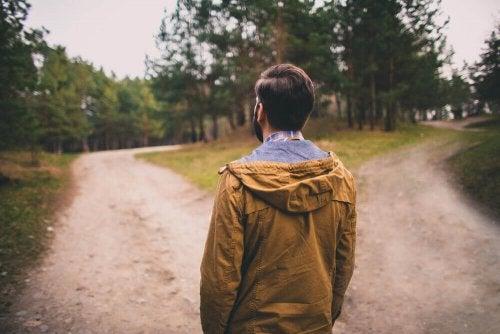 Uomo ad un bivio che sceglie quale strada percorrere per arrivare più vicino ai suoi sogni