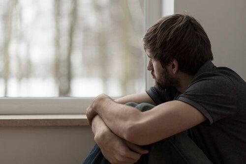 Uomo triste che guarda fuori dalla finestra pensando ai suoi problemi nell'esprimere emozioni