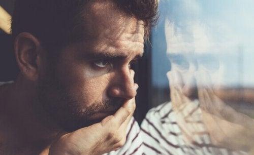 Uomo triste che guarda fuori da un finestrino, come rappresentazione delle frasi di Anna Freud
