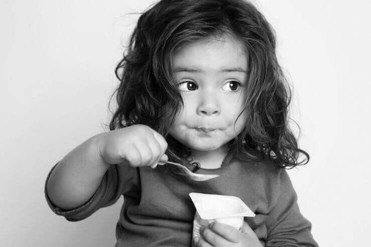 Bambina che mangia uno yogurt