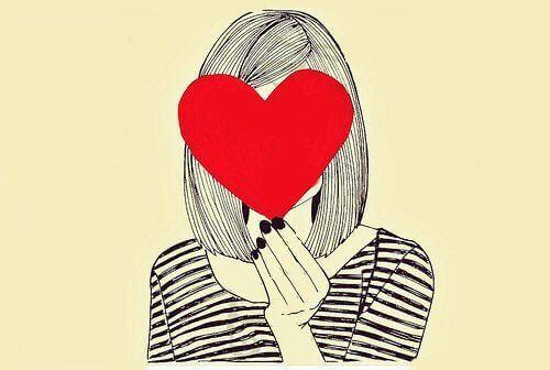Donna si copre il volto con un cuore