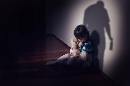 Bambina che abbraccia orsacchiotto per paura dei maltrattamenti.