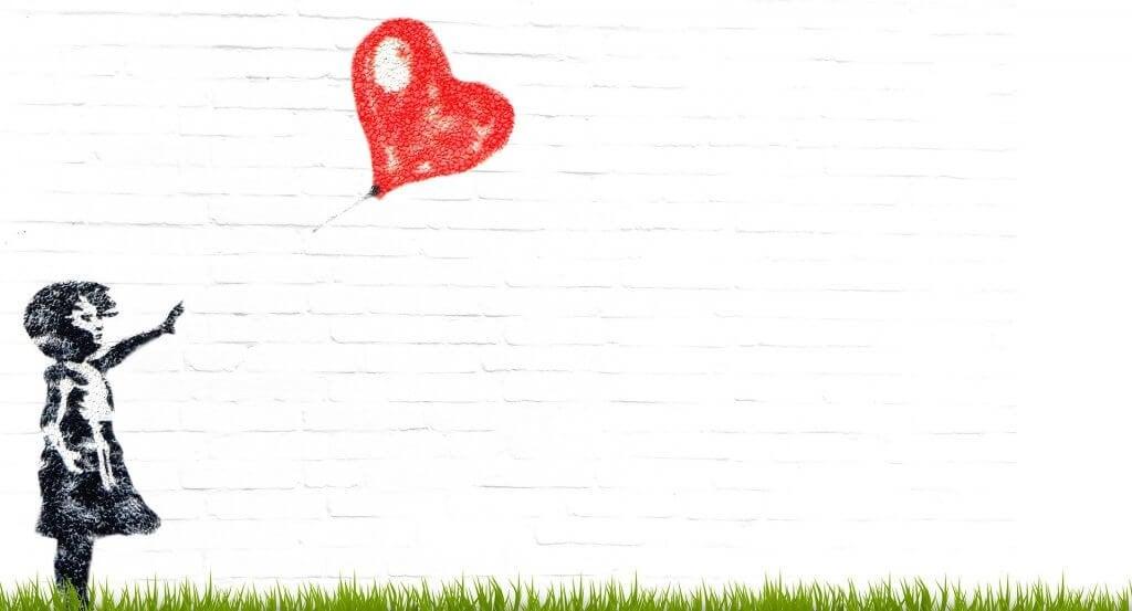 Bambina che lascia nadare un palloncino rosso a forma di cuore