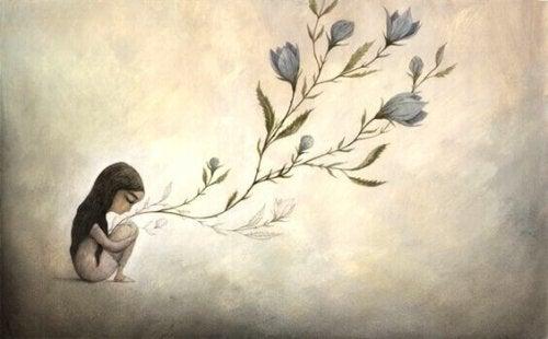 Bambina seduta con fiori teoria psicosociale dello sviluppo