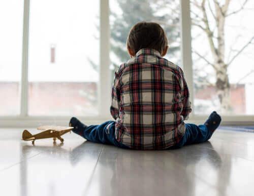 Bambino autistico seduto da solo