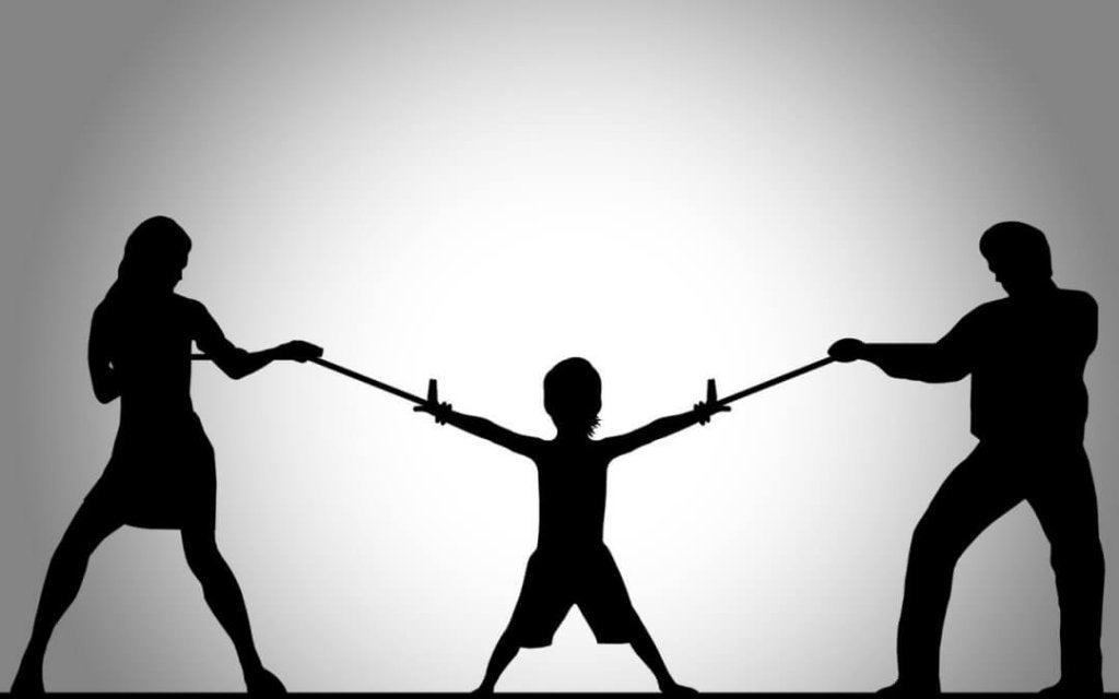 Genitori che tirano le braccia del figlio con una fune