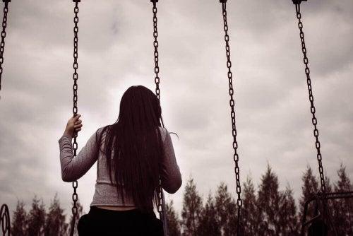 Donna sull'altalena mentre pensa a com'è difficile dire addio