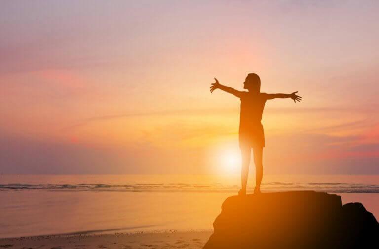Donna con le braccia aperte e tramonto