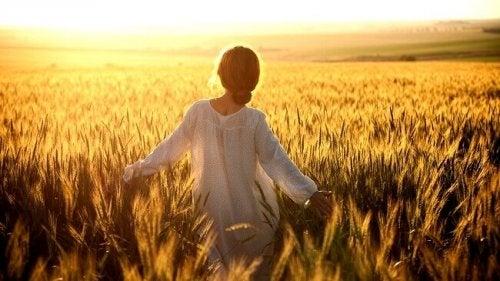 Donna che cammina in campo di grano