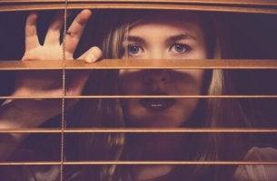 Donna con agorafobia che guarda dalla finestra