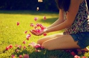 Donna con fiori fra le mani che ha il coraggio di nascere