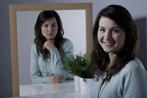 Donna contenta con riflesso nello specchio triste