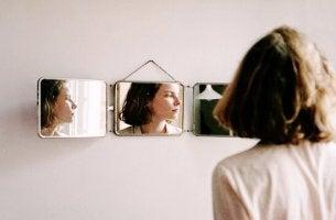 Donna davanti allo specchio che osserva la vulnerabilità