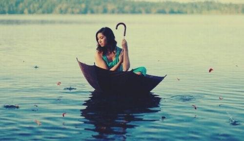 Donna all'interno di un ombrello che galleggia su un lago