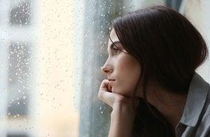 Donna triste affacciata alla finestra