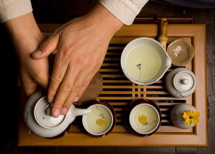 Mani che reggono una teiera durante la cerimonia del tè
