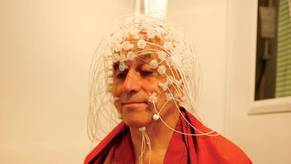 Matthieu Ricard con degli elettrodi in testa