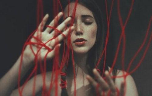Ragazza circondata da fili rossi che cerca di essere la miglior alleata di sé stessa