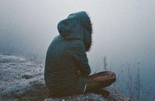 Ragazza seduta da sola, mentre pensa agli eccessi e ai vuoti