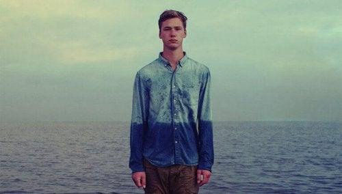 Ragazzo di fronte al mare con camicia bagnata