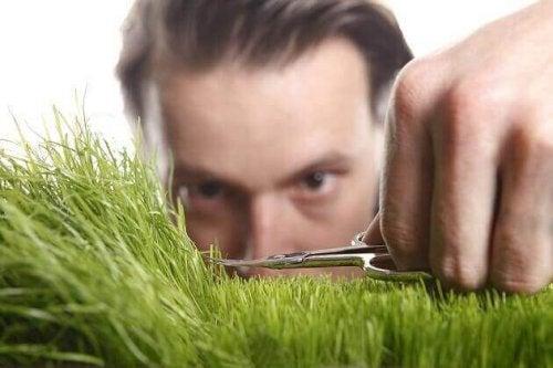 Uomo con disturbo della personalità ossessiva mentre taglia un cespuglio