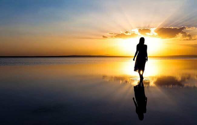 Donna cammina sulla spiaggia all'alba