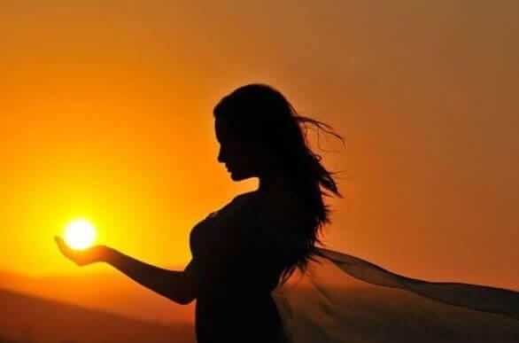 Donna sostiene il sole con le mani
