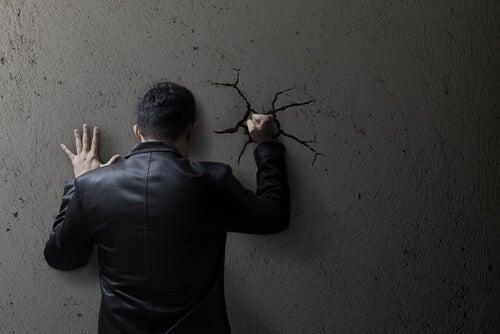 Ragazzo che dà un pugno al muro per la rabbia