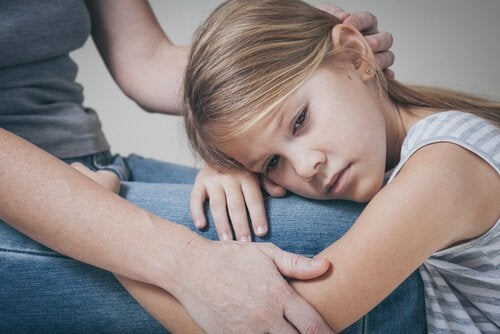 Bambina triste abbracciata alla madre