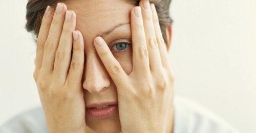 Donna che si copre il volto con le mani