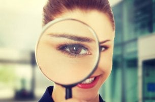 Donna curiosa con lente d'ingrandimento la curiosità