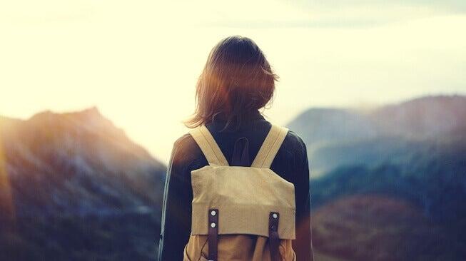 Donna di fronte a montagna viaggiare da soli